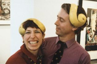 Karen Feinberg and Roger Haile wearing grapefruit peel caps at exhibition opening.